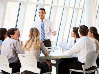 Business People Having Board Meeting In Modern Office Smiling