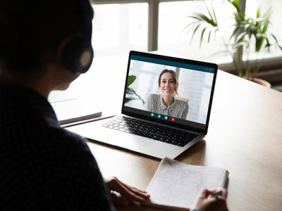 Back view of female employee sit at desk at home have Webcam conference on laptop with business partner or client, woman worker talk on video call with coworker or consultant, watch online webinar
